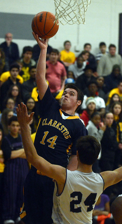 . Clarkston\'s #14 Nick Owens shoots over Bloomfield Hills #24 Nathan Graham during their game at Bloomfield Hills High School, Tuesday January 28, 2014. Bloomfield Hills went on to win the game 74-62. (Vaughn Gurganian-The Oakland Press)