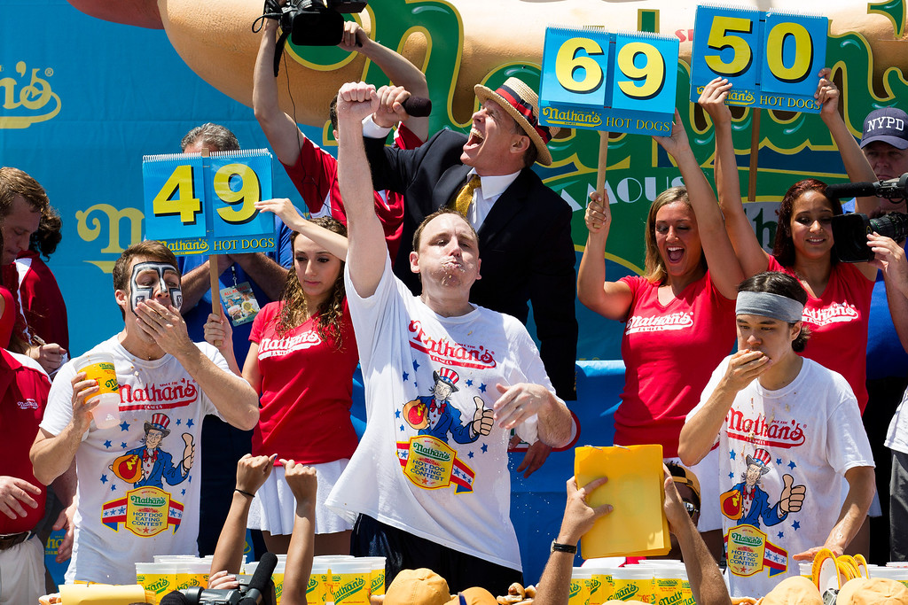 . Joey Chestnut, center, wins the Nathan\'s Famous Fourth of July International Hot Dog Eating contest with a total of 69 hot dogs and buns, alongside Tim Janus, left, and Matt Stonie, right, Thursday, July 4, 2013 at Coney Island, in the Brooklyn borough of New York. (AP Photo/John Minchillo)