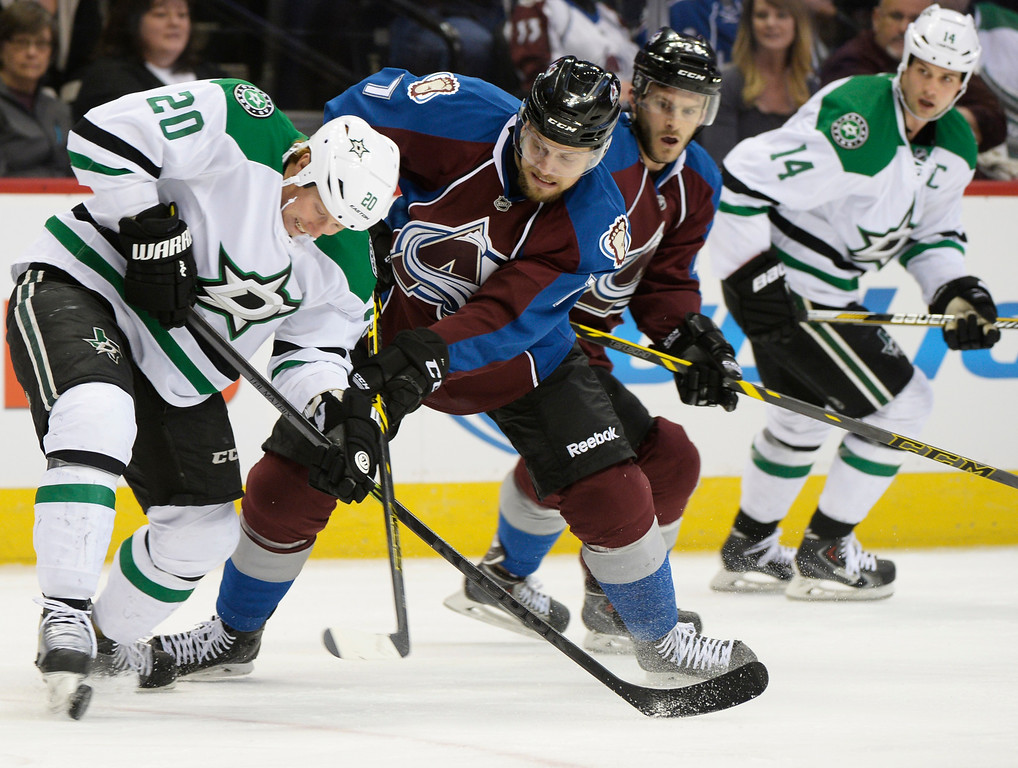 . Dallas Stars center Cody Eakin (20) tries to keep possession away from Colorado Avalanche center John Mitchell (7) during the first period Saturday, February 14, 2015 at the Pepsi Center in Denver, Colorado. (Photo By Brent Lewis/The Denver Post)