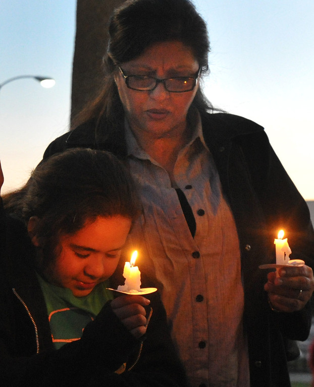 . Rose Limon holds her granddaughter, Ariana, 9, during a community-wide prayer vigil at Central Park in Whittier in response to recent attempted child abductions on Friday March 15, 2013. About 150 people attended the candlelight vigil led by Pastor Sam Gamboa of the Good Shepherd Family Bible Church and organized by the Whittier Area Evangelical Ministerial Alliance. City and police officials joined citizens and area church members as they prayed for protection of the children and the arrest of the suspects. (SGVN/Staff Photo by Keith Durflinger)