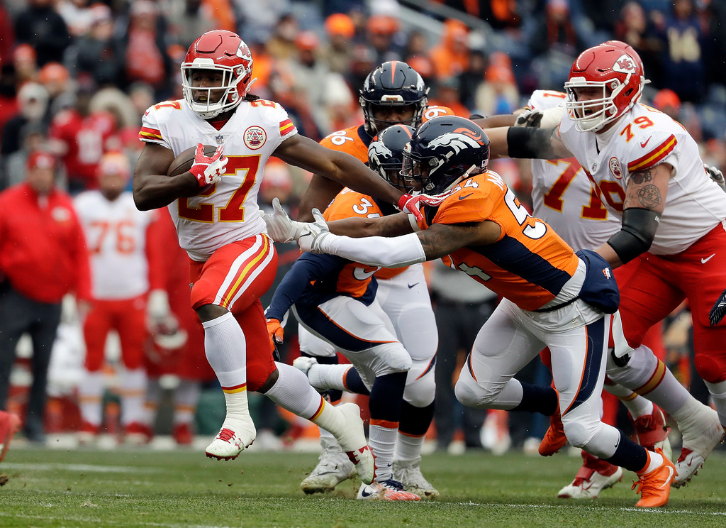 . Kansas City Chiefs running back Kareem Hunt (27) runs for a touchdown past Denver Broncos inside linebacker Brandon Marshall during the first half of an NFL football game Sunday, Dec. 31, 2017, in Denver. (AP Photo/Jack Dempsey)