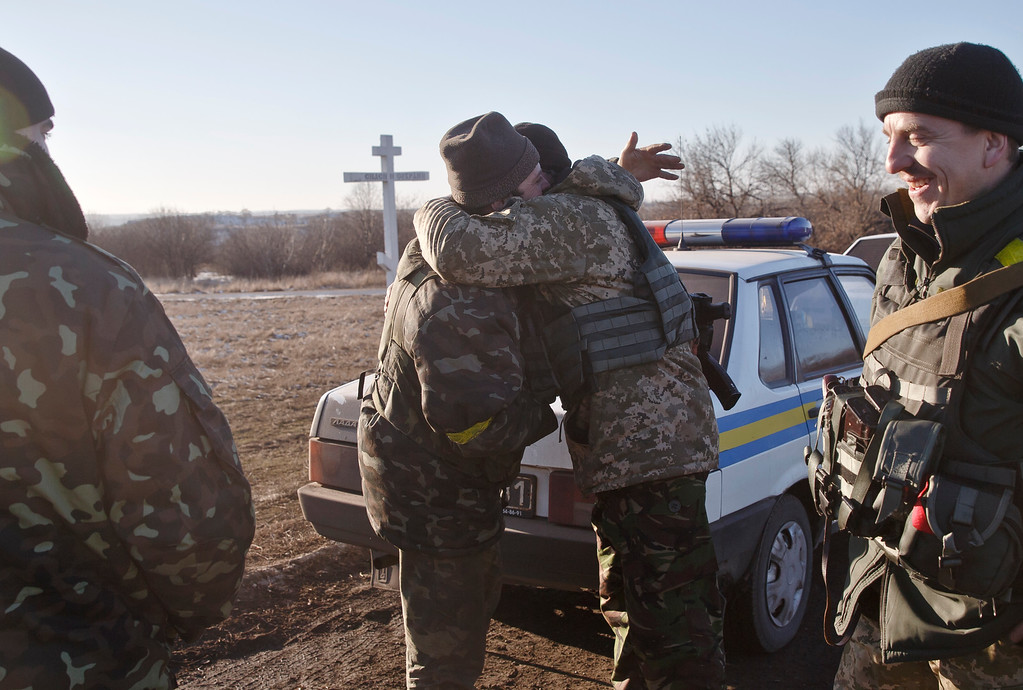 . Ukrainian servicemen hug outside Artemivsk, Ukraine, while pulling out of Debaltseve, Wednesday, Feb. 18, 2015. After weeks of relentless fighting, the embattled Ukrainian rail hub of Debaltseve fell Wednesday to Russia-backed separatists, who hoisted a flag in triumph over the town. The Ukrainian president confirmed that he had ordered troops to pull out and the rebels reported taking hundreds of soldiers captive.(AP Photo/Vadim Ghirda)