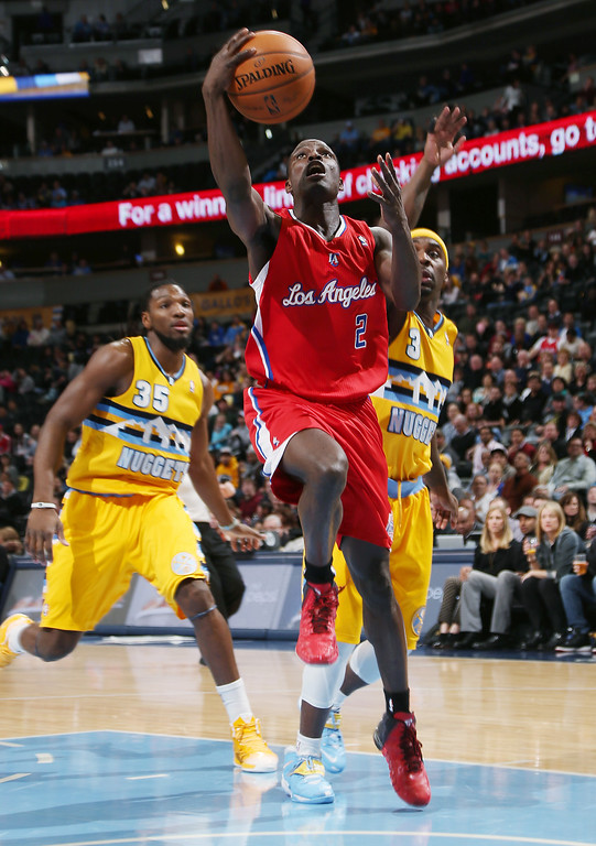 . Los Angeles Clippers guard Darren Collison, center, drives to the basket past Denver Nuggets forward Kenneth Faried, left, and guard Ty Lawson in the first quarter of an NBA basketball game in Denver, Monday, Feb. 3, 2014. (AP Photo/David Zalubowski)