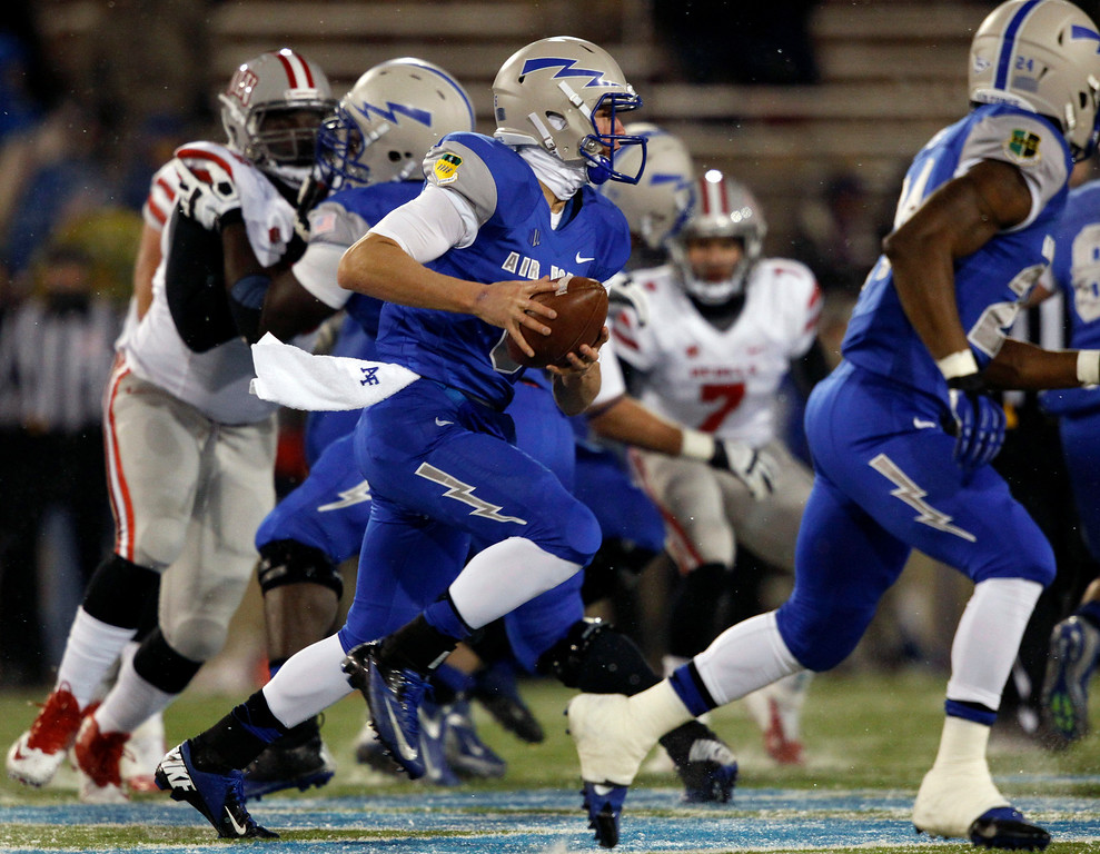 . Air Force quarterback Nate Romine, center, runs for a short gain against UNLV in the first quarter of an NCAA football game at Air Force Academy, Colo., on Thursday, Nov. 21, 2013. (AP Photo/David Zalubowski)