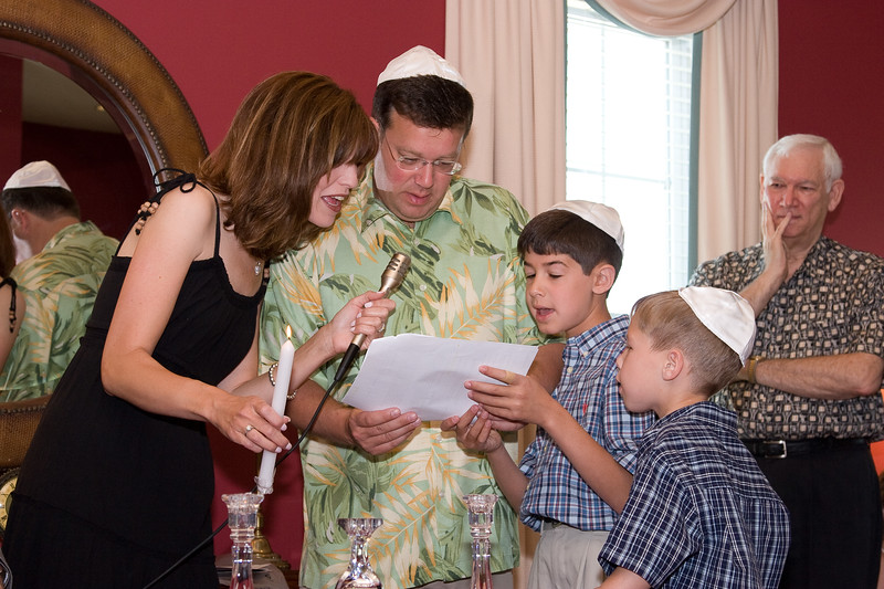 The Berenzweigs (Rachel, Seth, Josh, Adam) light the first candle and recite the blessing at cousin's baby naming.