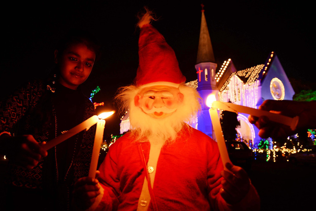 . An Indian child dressed as Santa Claus poses for a photograph while helping others light candles during Christmas eve celebrations at the illuminated St Paul\'s church in Amritsar on December 24,2013. Despite Christians forming a little over two percent of the billion plus population in India, with Hindus comprising the majority, Christmas is celebrated with fanfare and zeal throughout the country.  NARINDER NANU/AFP/Getty Images