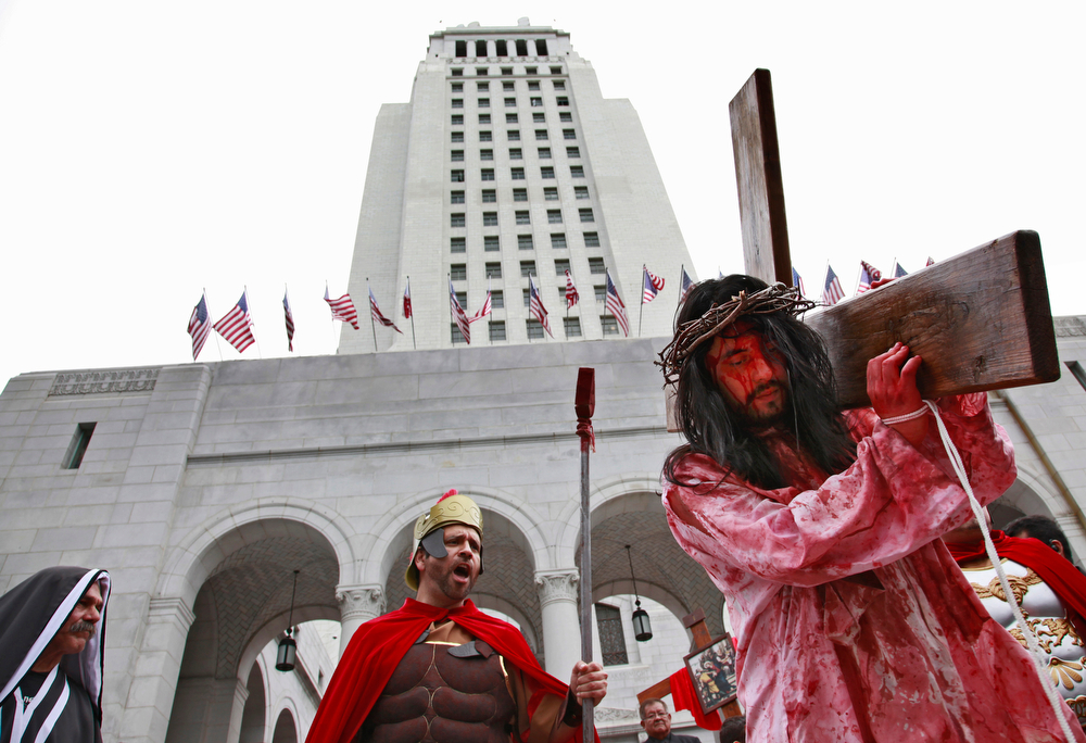 . Portraying Jesus Christ, a parishioner reenacts the steps of Jesus\' final hours, during a Good Friday procession in front of city hall in downtown Los Angeles on Friday, April 18, 2014. (AP Photo/Richard Vogel)