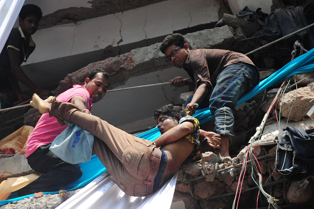 . Volunteers carry the body of a garment worker after an eight-story building collapsed in Savar, on the outskirts of Dhaka, on April 24, 2013.   AFP PHOTO/Munir uz ZAMAN/AFP/Getty Images