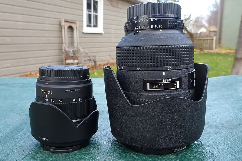 Mid-range zooms.  Panasonic 14-42mm f/3.5-5.6 (28-84mm @ 35mm equivalent) vs the Nikon 28-70mm f/2.8.