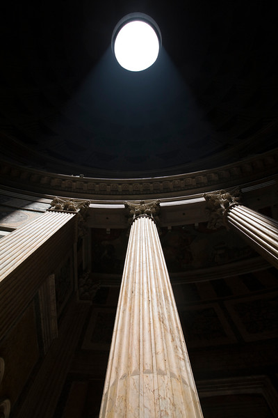 The dome oculus of the Pantheon casting a beam of sunlight on the Cornthian columns, Rome