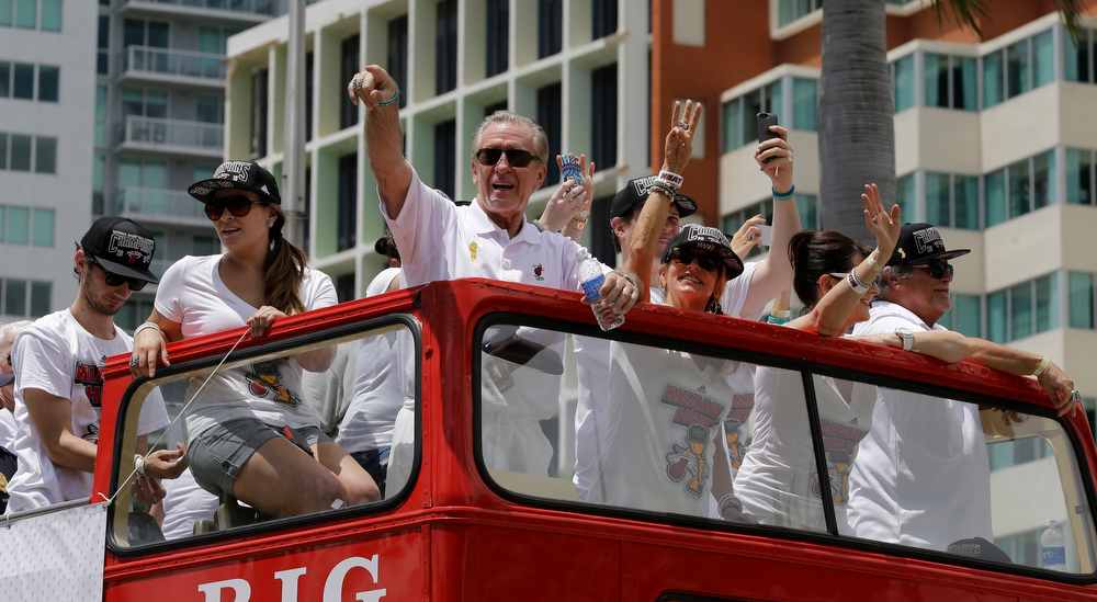 . NBA champion Miami Heat president Pat Riley, center,  points to fans during a parade honoring the team in Miami, Monday, June 24, 2013.  (AP Photo/Alan Diaz)
