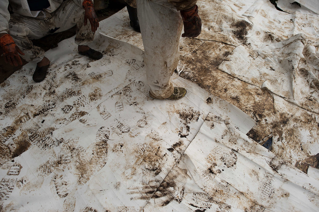 . Oil-stained footprints left behind by Royal Thai Navy personnel are seen as they take a break from cleaning up a beach from a major oil slick on Ao Phrao beach on the island of Ko Samet on July 30, 2013. Thai navy personnel battled to clean up a major oil slick which coated a beach on a popular tourist island in a national park after a pipeline leak.   NICOLAS ASFOURI/AFP/Getty Images
