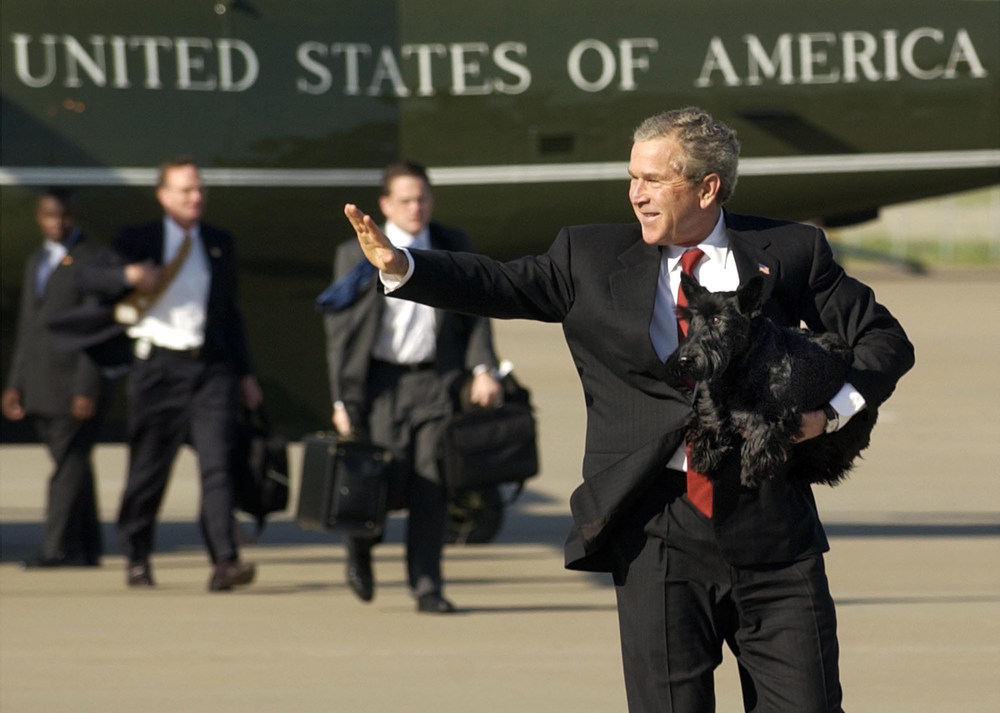 Description of . President Bush waves as he departs TSTC Airport in Waco, Texas with his dog Barney Monday, March 29, 2004.  The President spent the weekend on his ranch in nearby Crawford. (AP Photo/Gerald Herbert)
