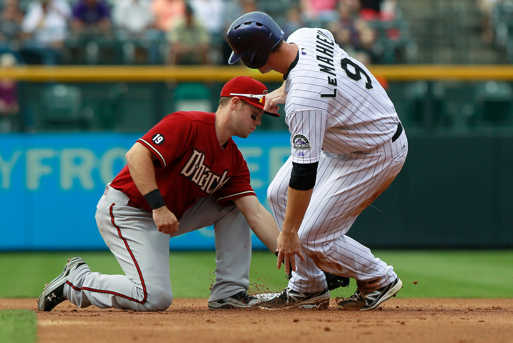 . Arizona Diamondbacks shortstop Chris Owings, left, applies the tag to put out Colorado Rockies\' DJ LeMahieu tries to steal second base in the first inning of a baseball game in Denver on Sunday, Sept. 22, 2013. (AP Photo/David Zalubowski)