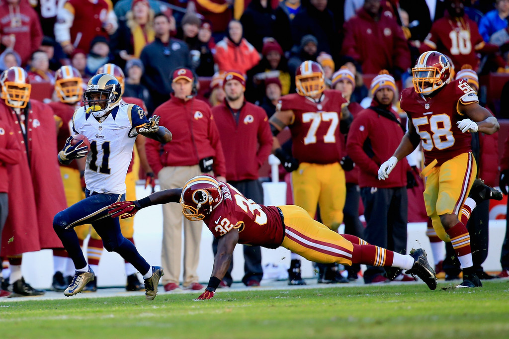 . LANDOVER, MD - DECEMBER 07:  Wide receiver Tavon Austin #11 of the St. Louis Rams avoids the tackle by running back Silas Redd #32 of the Washington Redskins as he scores a third quarter punt return touchdown at FedExField on December 7, 2014 in Landover, Maryland.  (Photo by Rob Carr/Getty Images)