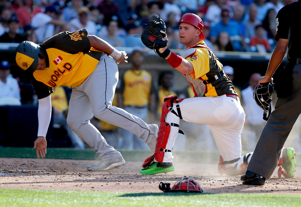 . World Team\'s Josh Naylor, of the Miami Marlins, is out at the plate as U.S. Team\' Kelly Carson, of the St. Louis Cardinals, holds onto the ball after the tag during the sixth inning of the All-Star Futures baseball game, Sunday, July 10, 2016, in San Diego. (AP Photo/Lenny Ignelzi)