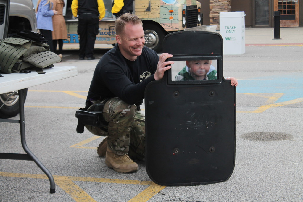 . Kristi Garabrandt � The News-Herald <br> Mentor SWAT officer Donnie Swindell holds a shield used by the SWAT Team while his two-year-old son Donnie looks through it during the 36th Annual Heroes Day held at Great Lakes Mall, May 12, 2018.