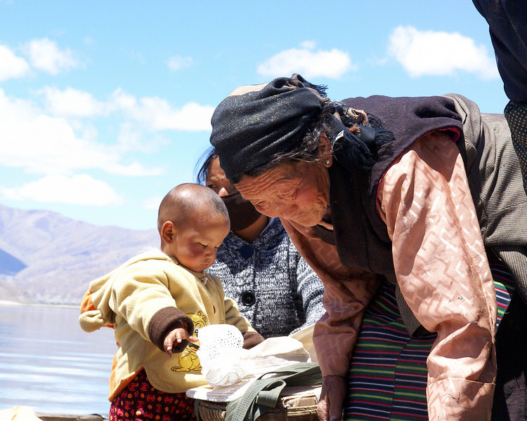 Tibetan boy, mother and grandmother on the ferry on the Yarlung.