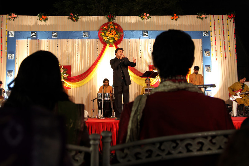 The bride and groom listen to a singer perform.