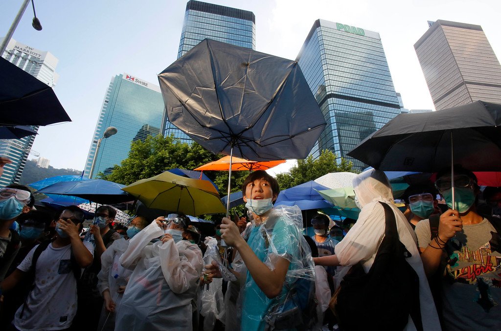 . A student protester uses an umbrella to block pepper spray from riot police as thousands of protesters surround the government headquarters in Hong Kong Sunday, Sept. 28, 2014. Hong Kong police used tear gas on Sunday and warned of further measures as they tried to clear thousands of pro-democracy protesters gathered outside government headquarters in a challenge to Beijing over its decision to restrict democratic reforms for the city. (AP Photo/Wally Santana)