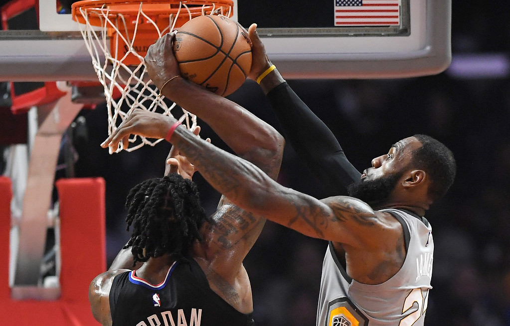 . Cleveland Cavaliers forward LeBron James, right, blocks the shot of Los Angeles Clippers center DeAndre Jordan during the first half of an NBA basketball game Friday, March 9, 2018, in Los Angeles. (AP Photo/Mark J. Terrill)