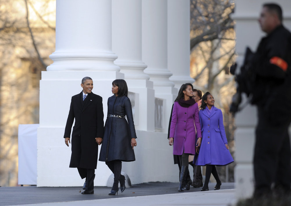 Description of . US President Barack Obama and wife Michelle Obama walk with daughters Sasha and Malia to the Reviewing Stand on Pennsylvania Avenue to watch the Parade during  the 57th Presidential Inauguration on January 21, 2013 in Washington, DC. ROD LAMKEY/AFP/Getty Images