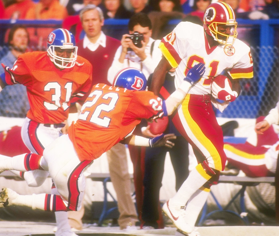 . Defensive lineman Tony Lilly #22 of the Denver Broncos tries to stop wide receiver Art Monk #81 of the Washington Redskins during the Super Bowl XXII game at the Jack Murphy Stadium in San Diego, California.  The Redskins won, 42-10.  Rick Stewart/Allsport