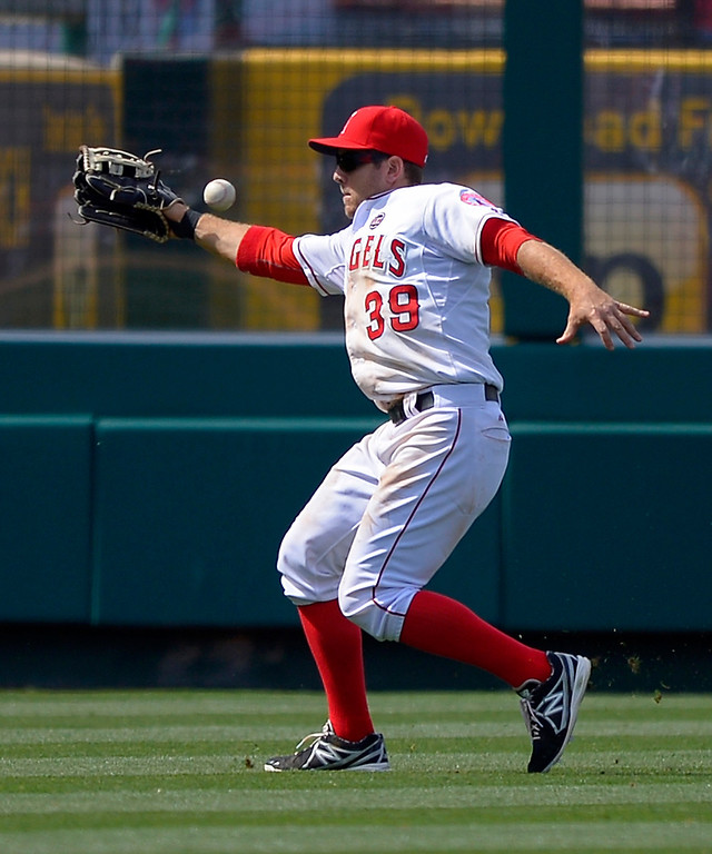 . Los Angeles Angels left fielder J.B. Shuck can\'t handle a ball hit for an RBI single by Pittsburgh Pirates\' Travis Snider during the 10th inning of their baseball game, Sunday, June 23, 2013, in Anaheim, Calif. Shuck was charged with an error on the play. (AP Photo/Mark J. Terrill)