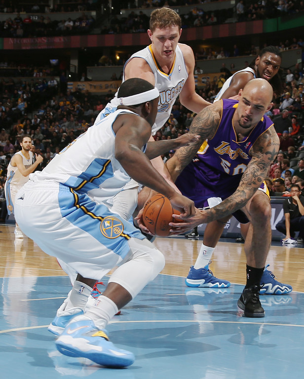 . Los Angeles Lakers center Robert Sacre, right, struggles to recover a loose ball as, from front left to back, Denver Nuggets guard Ty Lawson, center Timofey Mozgov, of Russia, and forward Kenneth Faried cover in the first quarter of an NBA basketball game in Denver on Friday, March 7, 2014. (AP Photo/David Zalubowski)