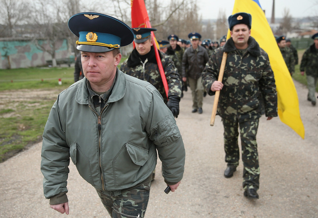 . Colonel Yuli Mamchor (L), commander of the Ukrainian military garrison at the Belbek airbase, leads his unarmed troops to retake the Belbek airfield from soldiers under Russian command in Crimea on March 4, 2014 in Lubimovka, Ukraine. After spending a tense night anticipating a Russian attack following the expiration of a Russian deadline to surrender, in which family members of troops spent the night at the garrison gate in support of the soldiers, Mamchor announced his bold plan to his soldiers early this morning. The Russian-lead troops fired their weapons into the air but then granted Mamchor the beginning of negotiations with their commander. Russian-lead troops have blockaded a number of Ukrainian military bases across Crimea.  (Photo by Sean Gallup/Getty Images)