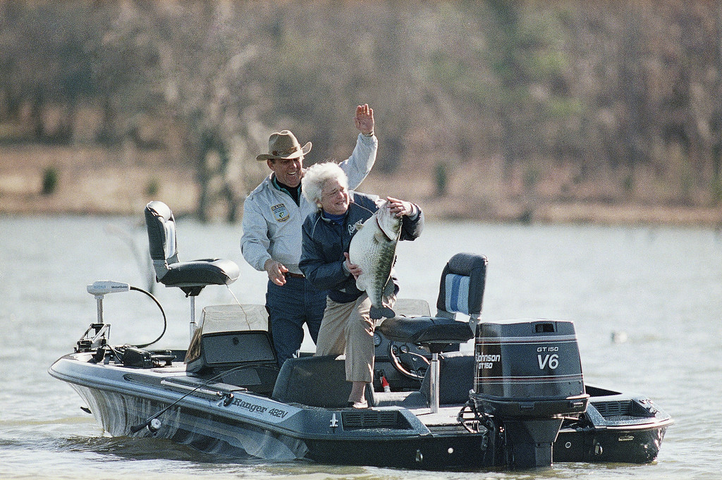 . First Lady Barbara Bush, center, holds a mounted large-mouth bass as she and fishing partner Ray Scott attempt to make the President think she caught the fish, Jan. 1, 1990, Pintlala, Ala. She and President Bush were in Pintlala on New Years Day for a bass fishing trip. (AP Photo/Ron Edmonds)