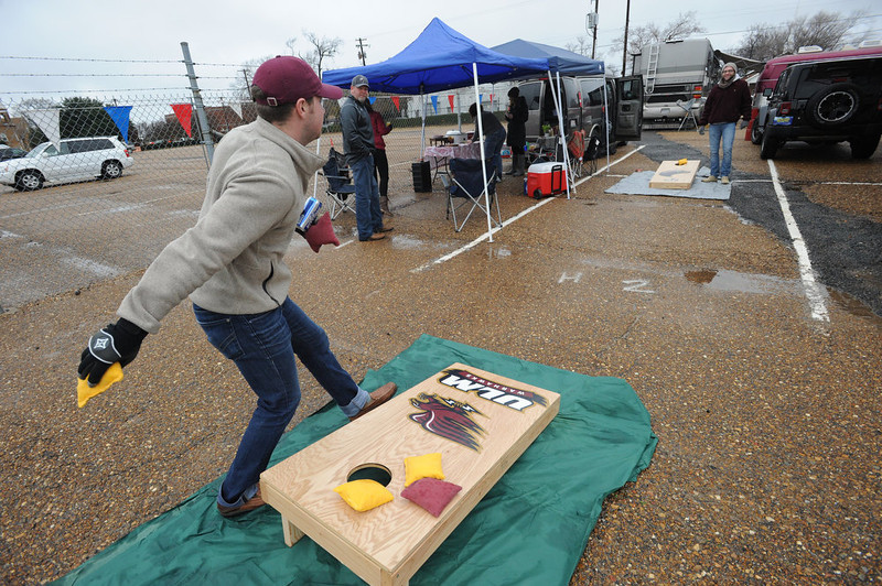 . Louisiana-Monroe fans Tucker Brown, left, and Tyson Brown play a game of corn hole while tailgating before the Independence Bowl NCAA college football game between Louisiana-Monroe and Ohio in Shreveport, La., Friday, Dec. 28, 2012. (AP Photo/The Shreveport Times, Douglas Collier)