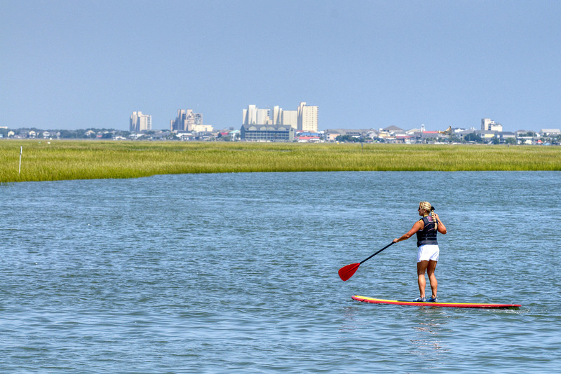 A woman paddleboards along the inlet with a view of Garden City Beach in the distance in Murrells Inlet, SC on Tuesday, September 10, 2013. Copyright 2013 Jason Barnette