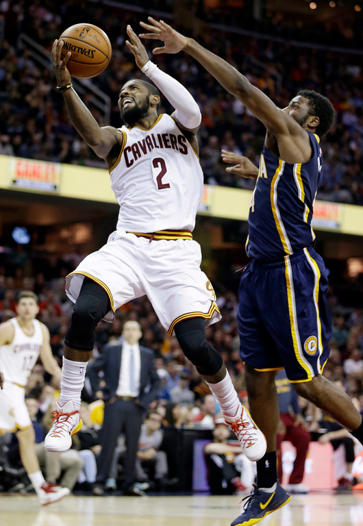 . Cleveland Cavaliers\' Kyrie Irving, left, drives to the basket against Indiana Pacers\' Solomon Hill, right, during an NBA basketball game Saturday, Nov. 29, 2014, in Cleveland. The Cavaliers defeated the Pacers 109-97. (AP Photo/Tony Dejak)
