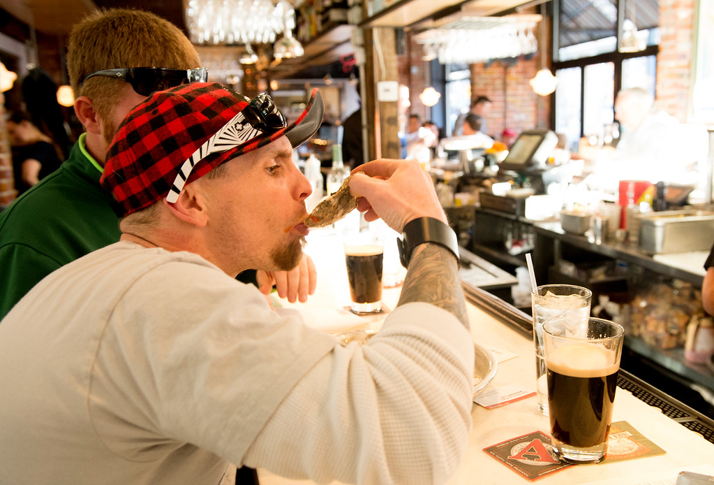 . With a couple of Guinness beers on the counter,  Frank Forbeau knocks back a Chesapeake Bay oyster during happy hour with friend Kevin Martin (behind Forbeau) at Jax Fish House and Oyster Bar in downtown Denver on Friday, February 26, 2016.   (Photo by Cyrus McCrimmon/ The Denver Post)