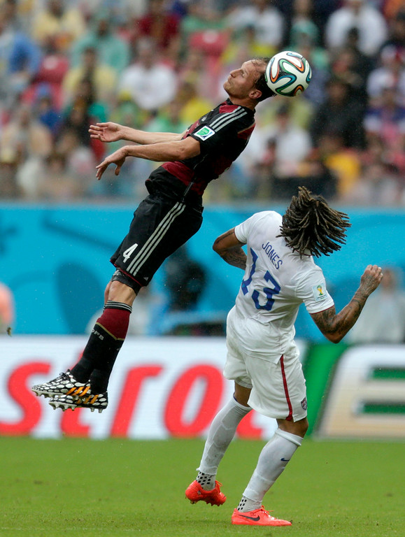 . Germany\'s Benedikt Hoewedes heads the ball over United States\' Jermaine Jones during the group G World Cup soccer match between the United States and Germany at the Arena Pernambuco in Recife, Brazil, Thursday, June 26, 2014. (AP Photo/Julio Cortez)