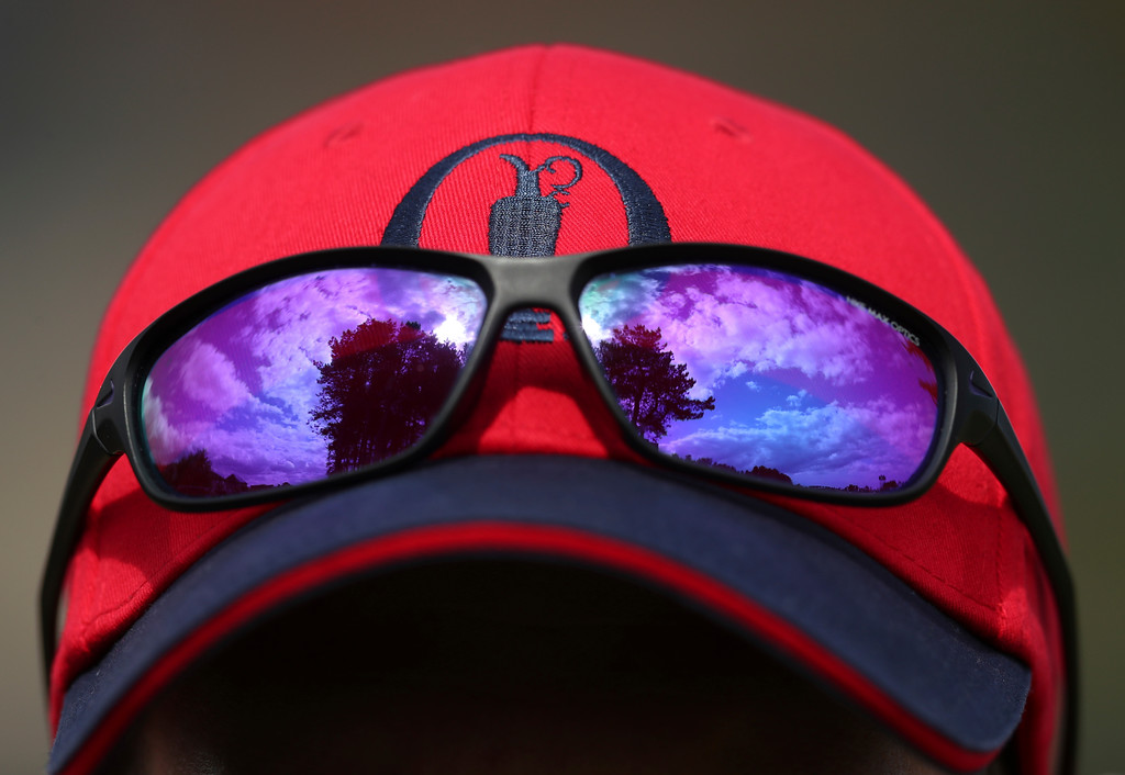 . The sky is reflected in a pair of sunglasses resting on a hat worn by an official during a practice round ahead of the British Open Golf Championship in Carnoustie, Scotland, Wednesday July 18, 2018. (AP Photo/Jon Super)