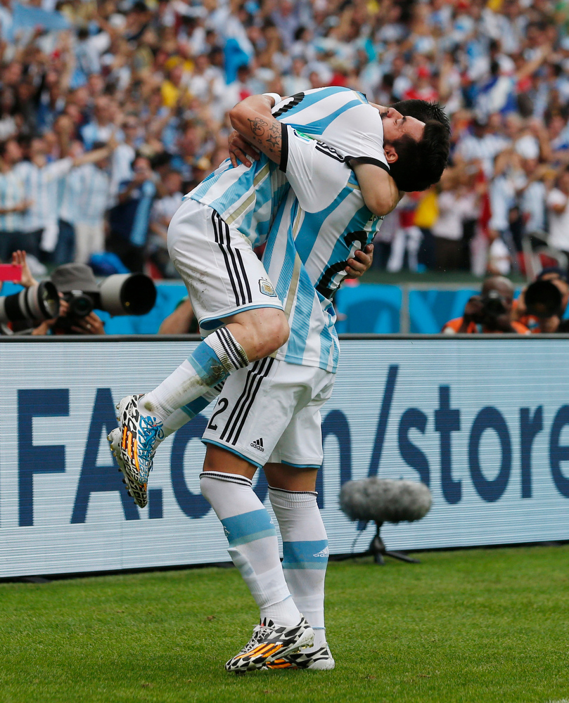 . Argentina\'s Lionel Messi, top, is hugged by his teammate Ezequiel Lavezzi after scoring his side\'s second goal during the group F World Cup soccer match against Nigeria at the Estadio Beira-Rio in Porto Alegre, Brazil, Wednesday, June 25, 2014. (AP Photo/Jon Super)