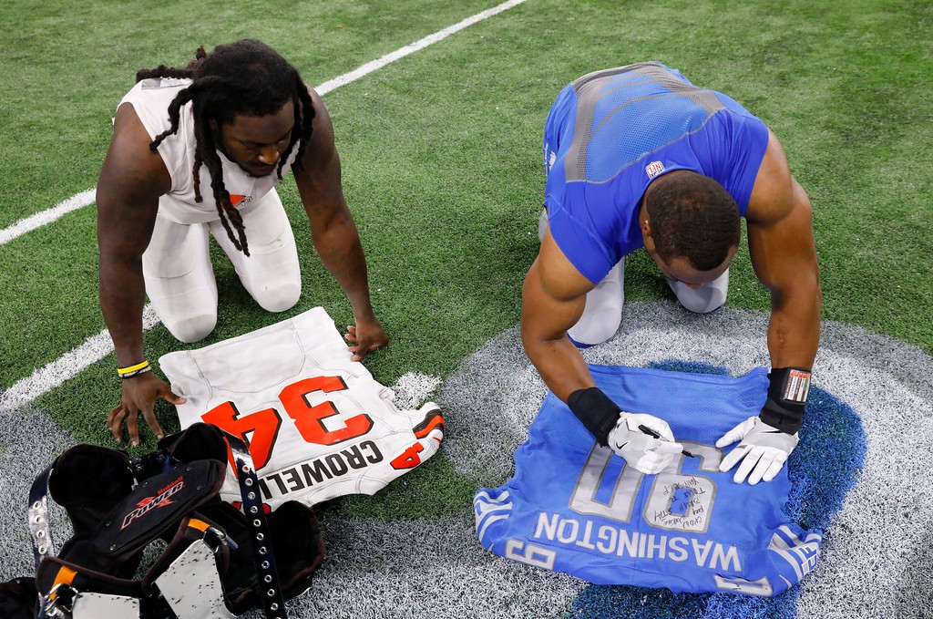 . Cleveland Browns running back Isaiah Crowell (34) and Detroit Lions defensive end Cornelius Washington (90) exchange jerseys after their NFL football game, Sunday, Nov. 12, 2017, in Detroit. (AP Photo/Jose Juarez)