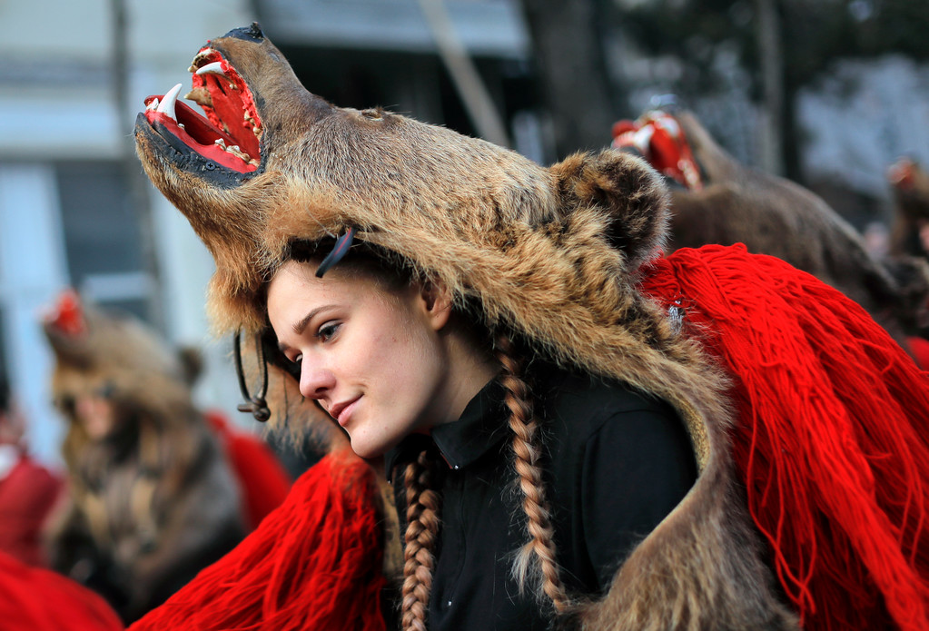 . A girl wearing a bear costume dances during an annual ritual in Piatra Neamt, northern Romania, Thursday, Dec. 28, 2017. The tradition, which originates in pre-Christian times when dancers wearing colored costumes or animal furs went from house to house in villages singing and dancing to ward off evil, has moved to Romania\'s cities, where dancers travel to perform the ritual for money.(AP Photo/Vadim Ghirda)