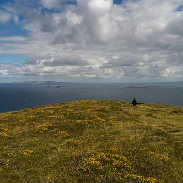 Hiker walking on the coastline from Brandon Point, Murirrigane, Brandon, County Kerry, Ireland