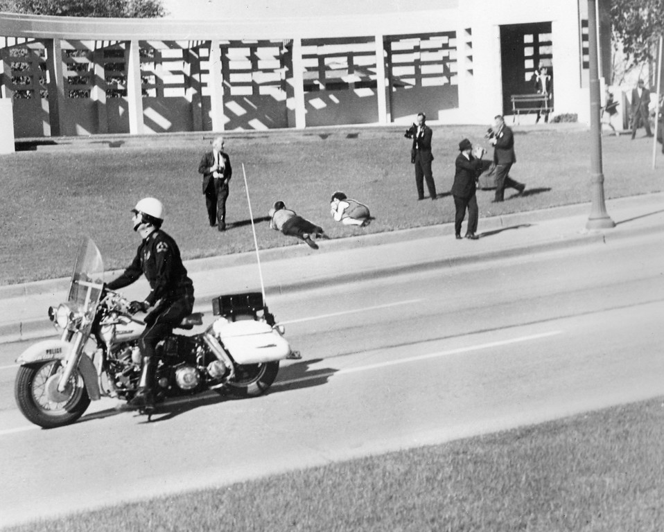 . As spectators lie on the ground in Dealey Plaza and cameramen roll their cameras, a motorcycle police officer drives by immediately after the shooting. Tom Dillard/Dallas Morning News