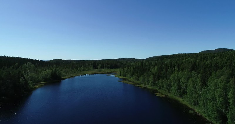 Aerial: 270 degrees panorama over a lake with a hill farm and a footbridge