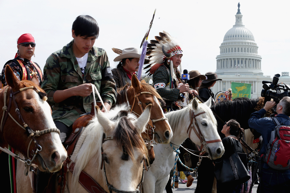 ". Members of the Cowboy and Indian Alliance, including Native Americans, farmers and ranchers from across the United States, hold a horseback ride while demonstrating against the proposed Keystone XL pipeline in front of the U.S. Capitol April 22, 2014 in Washington, DC. As part of its ""Reject and Protect\"" protest, the Cowboy and Indian Alliance is organizing a weeklong series of actions by farmers, ranchers and tribes to show their opposition to the pipeline.  (Photo by Chip Somodevilla/Getty Images)"