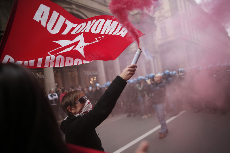 . Anti-riot policemen face demonstrators in Turin during one of several rallies against unemployment and austerity in Italy for May Day, on May 1, 2014.  Activists lobbed smoke bombs at police, who charged against the demonstrators in an industrial city that has been badly hit by a painful two-year recession. Thousands also took part in a peaceful demonstration called by the main trade unions in Pordenone, where the closure of a nearby washing machine plant owned by Sweden\'s Electrolux is putting 1,300 jobs at risk. (MARCO BERTORELLO/AFP/Getty Images)