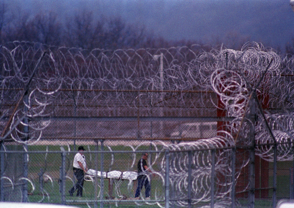 . The body of the seventh prisoner killed in a riot at the Southern Ohio Correctional Facility in Lucasville, Ohio, is removed, April 13, 1993. Prisoners are holding eight guards hostage in the siege that began on April 11. (AP Photo/Chris Kasson)
