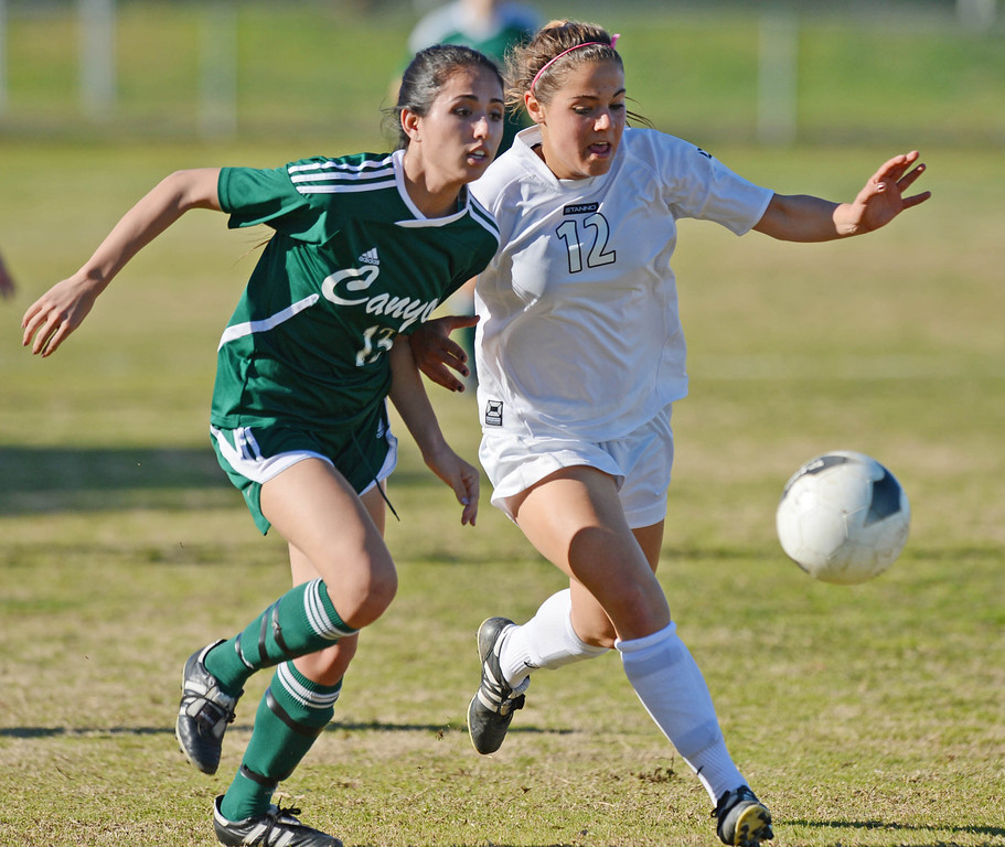 . Peninsula\'s Michelle Duarte (12) gets to the ball ahead of Canyon\'s Kristina Watanabe (13) in a CIF SS Division II first round soccer game Thursday in Rolling Hills Estates. After Peninsula seemingly dominated most of the game, Canyon scored a goal in the final two minutes to win 1-0. 20130214 Photo by Steve McCrank / Staff Photographer