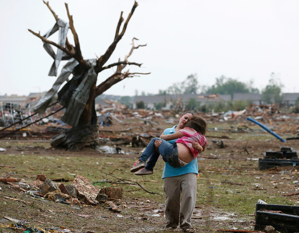 . In this May 20, 2013, file photo, LaTisha Garcia carries her 8-year-old daughter, Jazmin Rodriguez, near Plaza Towers Elementary School after a massive tornado carved its way through Moore, Okla., leaving little of the school and neighborhood. (AP Photo/Sue Ogrocki, File)