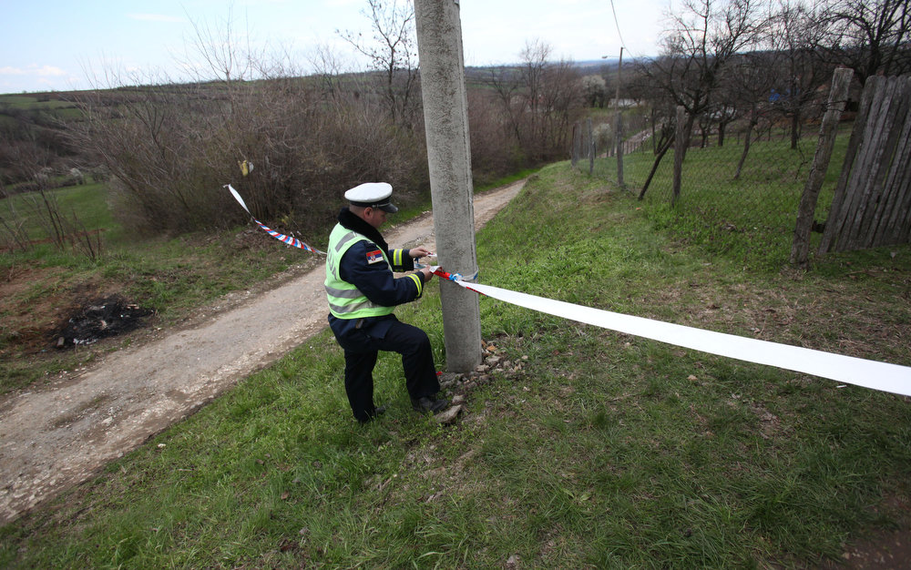 . A police officer prepares police tape in the village of Velika Ivanca, Serbia, Tuesday, April 9, 2013. A 60-year-old man gunned down 13 people, including a baby, in a house-to-house rampage in the quiet village on Tuesday before trying to kill himself and his wife, police and hospital officials said. Belgrade emergency hospital spokeswoman Nada Macura said the man, identified as Ljubisa Bogdanovic, used a handgun in the shooting spree at five houses. The dead included six women. (AP Photo/Darko Vojinovic)