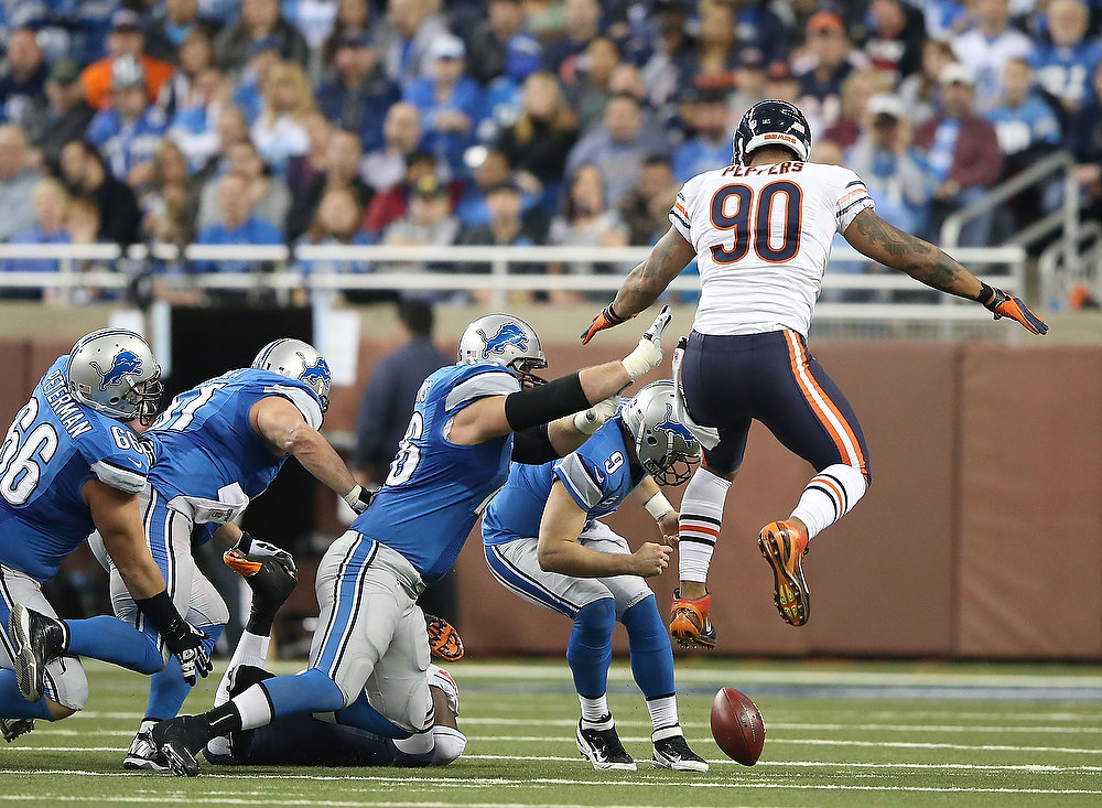 . Matthew Stafford #9 of the Detroit Lions attempts to pick up the fumbled ball as Julius Peppers #90 of the Chicago Bears gives chase during the third quarter of the game at Ford Field on December 30, 2012 in Detroit, Michigan. The Bears defeted the Lions 26-24.  (Photo by Leon Halip/Getty Images)